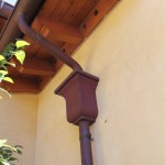 Half Round Copper Gutter with cast bronze scroll straps, custom copper leaderheads